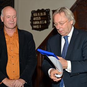Zou hij het mooi vinden? De overhandiging van het eerste exemplaar van het boek in discrete verpakking door Anton Scheepstra (uitgeverij Passage) aan Peter den Oudsten (burgemeester van Groningen).