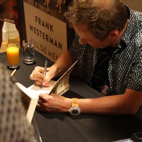 Al vrij snel vormt zich een enorme rij. Na een boek te hebben aangeschaft is het wachten in de signeer-rij.Frank heeft het druk!