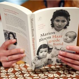 Een bezoeker leest 'Haar goede hand' van Marion Bloem.