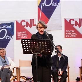 Anneke Brassinga draagt voor uit haar werk, op de achtergrond Margot Dijkgraaf en dichters K. Michel en Radna Fabias.