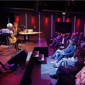 Een volle zaal in Desmet luistert zaterdagavond 15 juni naar een talkshow met host Elma Drayer, die NRC-journalist Marcel Haenen interviewt over zijn boek De Bokser, voorafgaand aan de uitzending van NOS Met het Oog op Morgen.