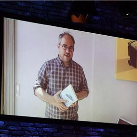 Genomineerde Arjen van Veelen – fysiek afwezig vanwege een vakantie – spreekt de zaal toe via een videoboodschap over zijn boek 'Amerikanen lopen niet. Leven in het hart van de VS' (De Correspondent).