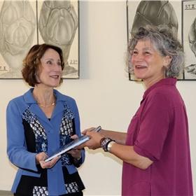 Het moment suprême: Carin Holtslag (r) overhandigt het eerste exemplaar van 'Heimweevogel' aan Louise Vet (l).