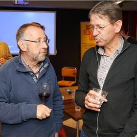 """Hans Loeve van boekhandel Riemer in Amersfoort (links) en zijn collega Sierk Spits van boekhandel Nawijn en Polak uit Apeldoorn (rechts) vinden bijeenkomsten als deze belangrijk voor hun netwerk. """"En we maken er een leuk dagje uit van"""", zegt Hans, """"met een goed glas wijn"""", vult Sierk aan."""