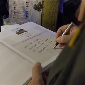 Gijs signeert na afloop een aantal boeken.