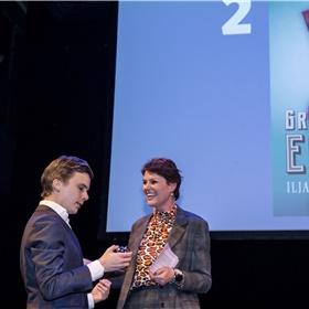 Bram Kleiweg (De Arbeiderspers) neemt de oorkonde in ontvangst voor het op één na bestverkochte boek van 2019: Pfeijffers 'Grand Hotel Europa'. En geeft Eveline Aendekerk een cadeautje: het belletje van de piccolo