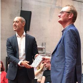 'Ik mag niet klagen', het actieboek van Bookstore Day. Giel van Strien (r) van WriteNow rijkt het eerste exemplaar uit aan wethouder Said Kasmi van cultuur.