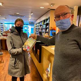 De allereerste klant bij boekhandel Logica in IJsselstein vanochtend. Rechts eigenaar Frits Mulder