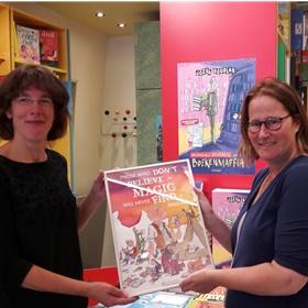 Dorothé Cras van de Utrechtse Kinderboekhandel krijgt de ingelijste poster uit handen van Maartje Beukers