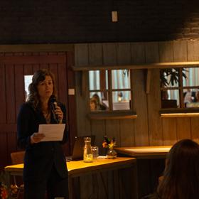 Redacteur Lisanne Matthijssen van HarperCollins spreekt de aanwezigen toe