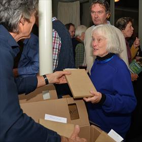 Roland van der Waal (vrijwilliger) geeft presentexemplaar aan Magda Bolt (klant). 'Ik woon inmiddels in de Achterhoek maar ik bestel mijn boeken hier. Het zijn zulke leuke mensen. Ze hebben maar een half woord nodig.'